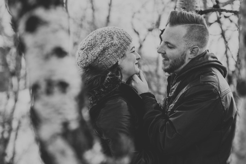 Couple laughs in between trees in Calgary during engagement session in black and white